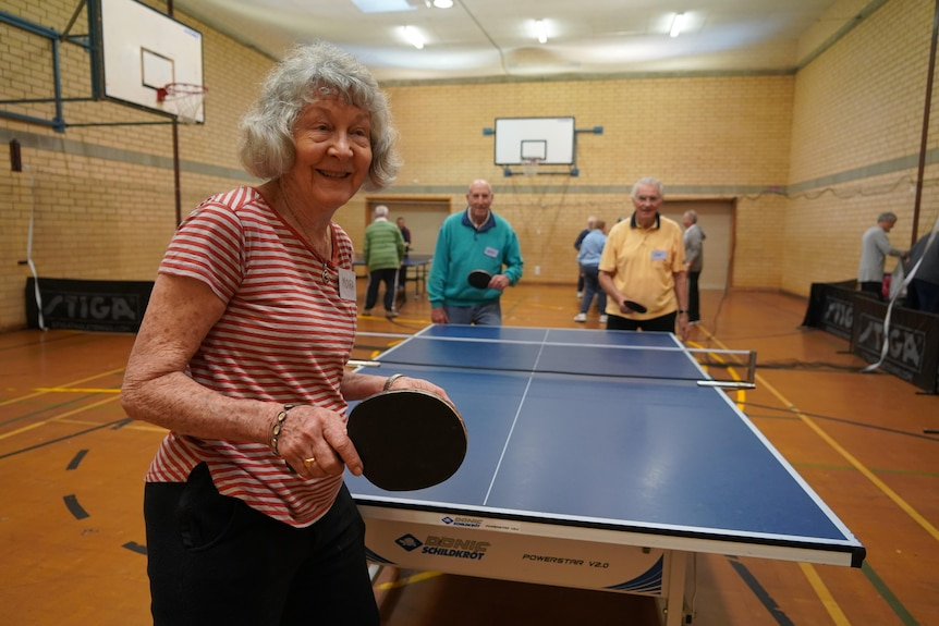 Three elderly people playing a game of table tennis