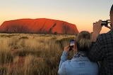 People taking photos of Uluru