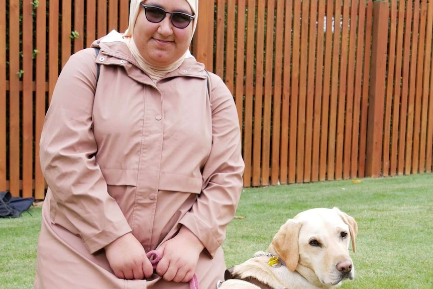 A blind woman in a head scarf with a guide dog