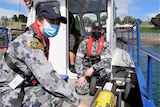 Two Navy personnel sit with an AUV on board a boat.