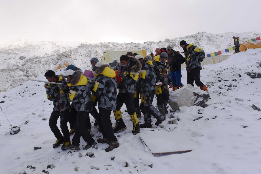 Rescuers stretcher injured to helicopter at Everest base camp