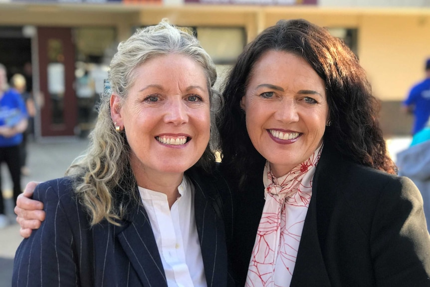 Libby Coker and her sister Janet stand with their arms about each other, outside a polling booth.