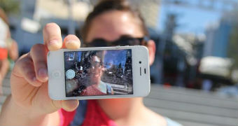 A woman holds an iPhone in front of her face and snaps a selfie.