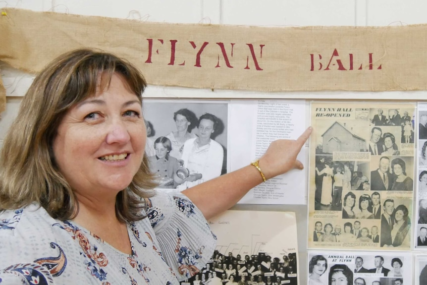 Andrea Norton pointing to a display about the Flynn Ball which was held in the hall