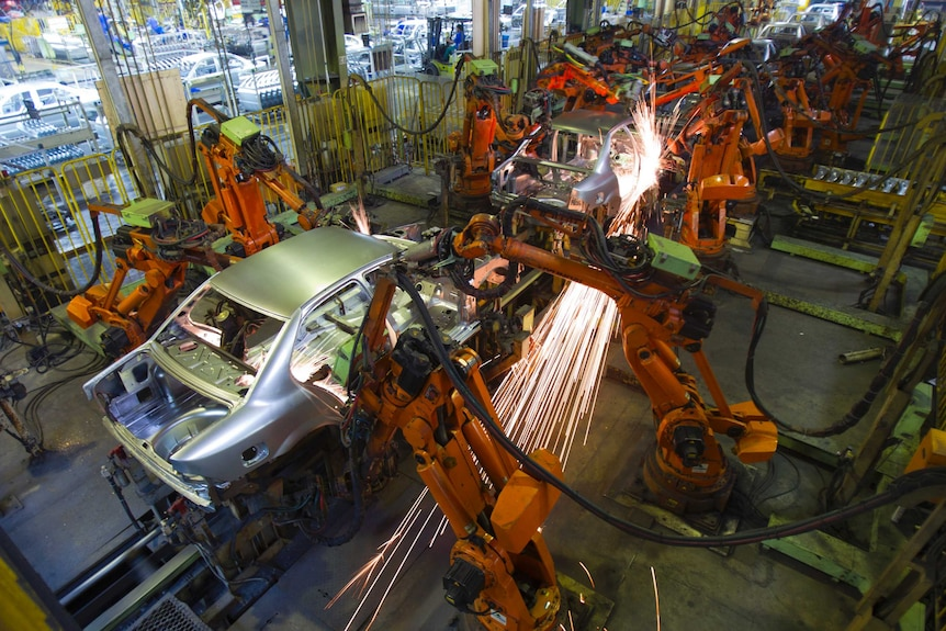 Robots work on cars in a workshop
