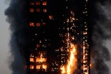 Flames and smoke billow from a burnt-out apartment building in London.