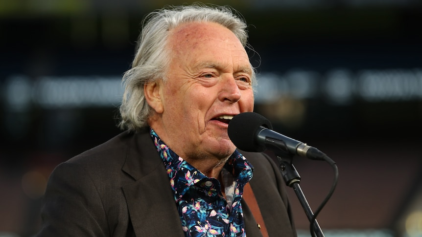 A close-up shot of a man in a floral shirt and jacket singing into a microphone.