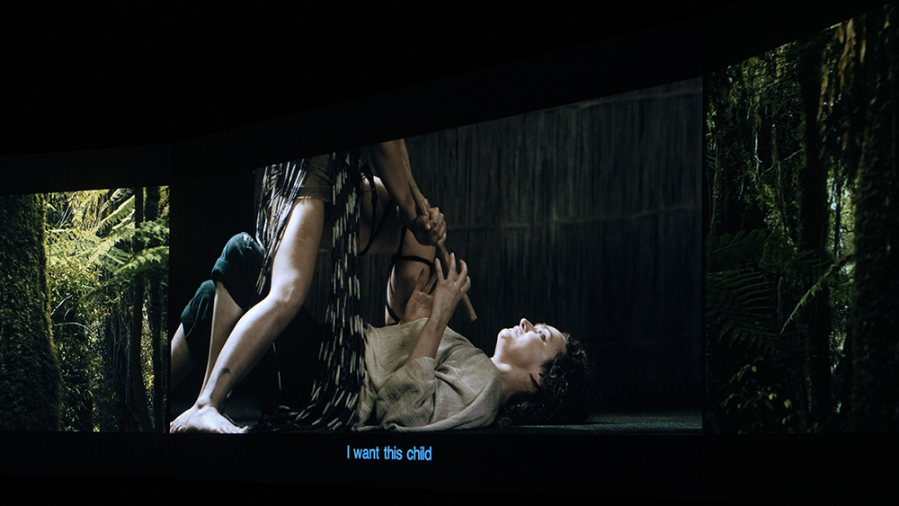 On a screen in a dark room, a woman stands over a scared looking woman and holds Taiaha or fighting staff weapon to her throat.
