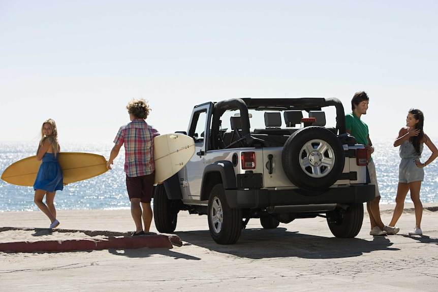 A family of four — two carrying surfboards — stand on a beach next two a four-wheel drive.