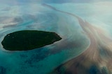An oil slick expands across a body of sea water near an island off the coast of Mauritius
