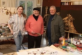 An elderly man and his two adult children stand in a busy art studio