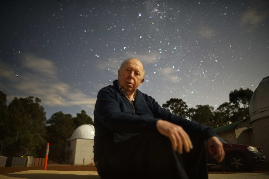 An elderly man sits in front of an observatory under a starry sky.