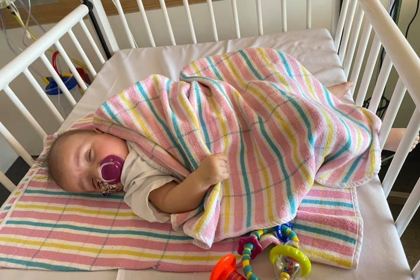 A baby named Willow sleeps in a crib with a pink blanket over her