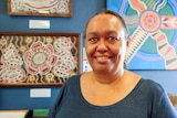 An Indigenous woman standing in front of Aboriginal artwork wearing a dark blue shirt