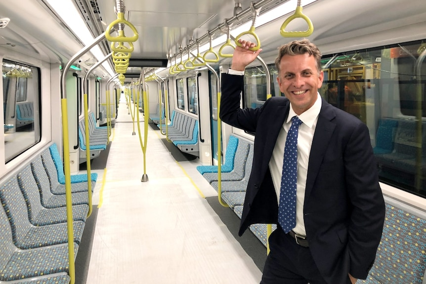 A man in a blue suit holds a handrail on a new train that has wrapping on its floor.