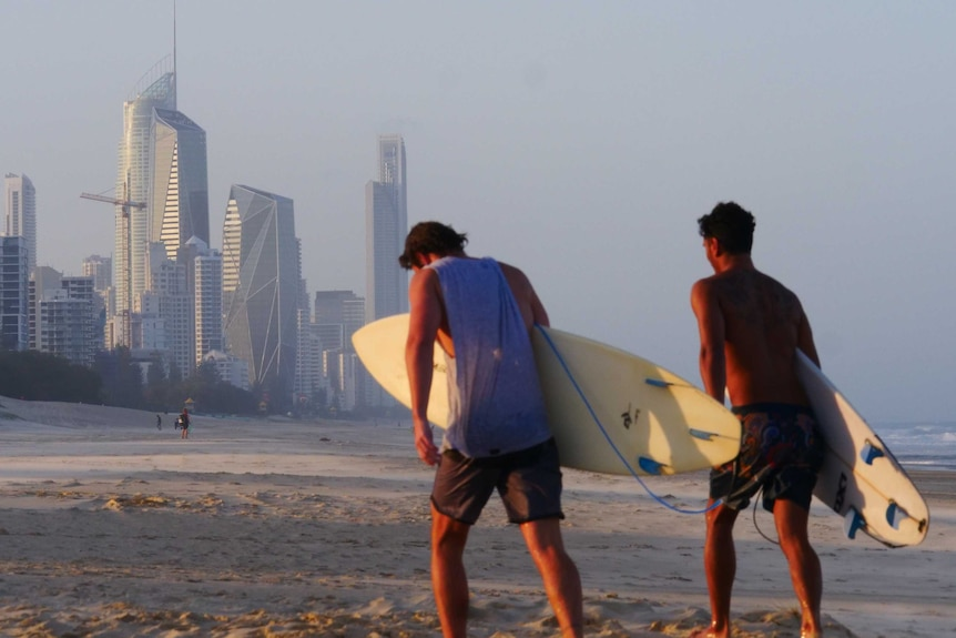 two surfers, skyline in background