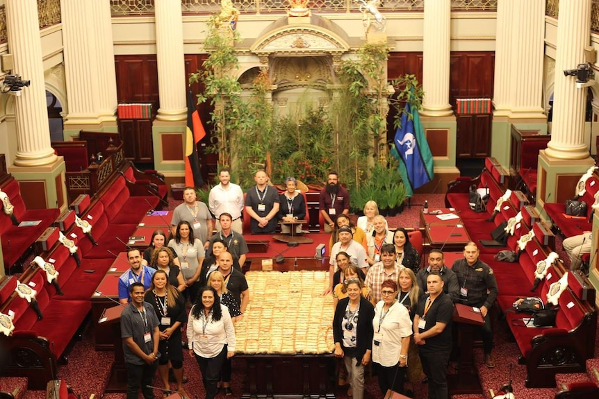 The First Peoples' Assembly members gather around a possum quilt inside the Parliament's Upper House.