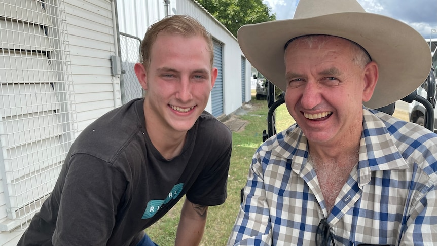 A man in a check shirt and a cowboy hat smiles. He is next to another younger man in a black shirt.
