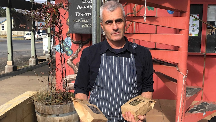 Tim Winbourne holds packets of pasta that he makes outside a delicatessen in Braidwood