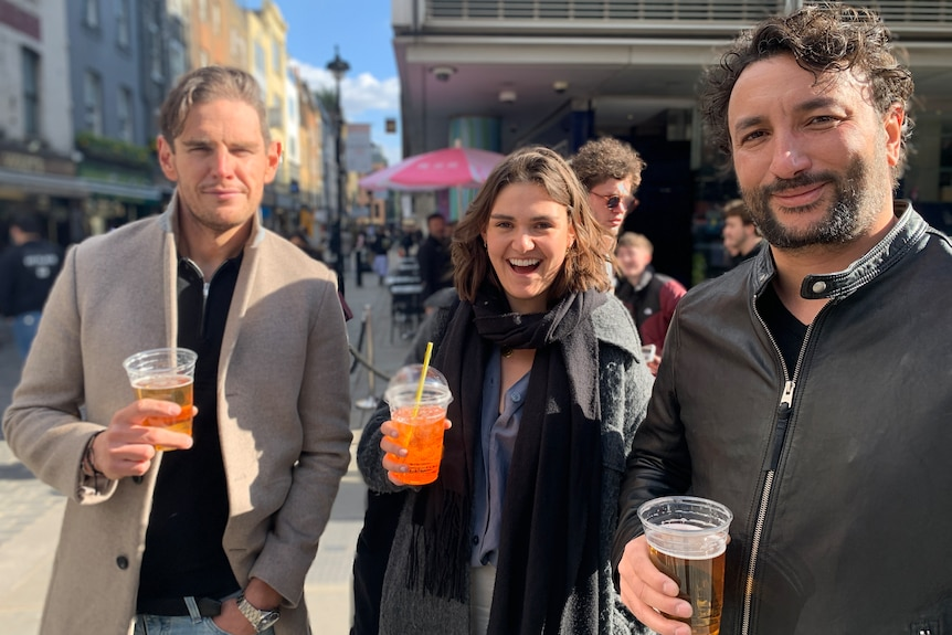 Two men and a woman hold their drinks and smile.