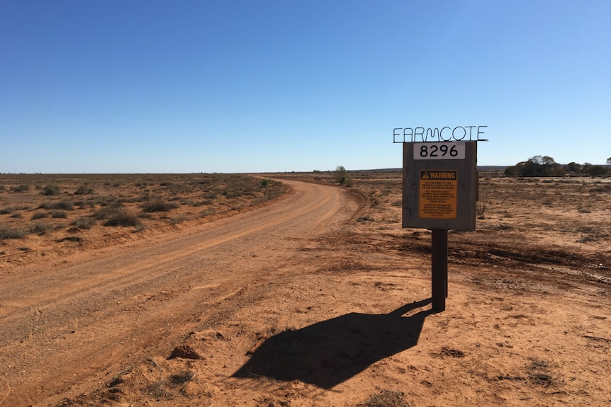 A dirt road winds past a sign for Farmcote station, surrounded by dry red earth with not a cloud in the sky.