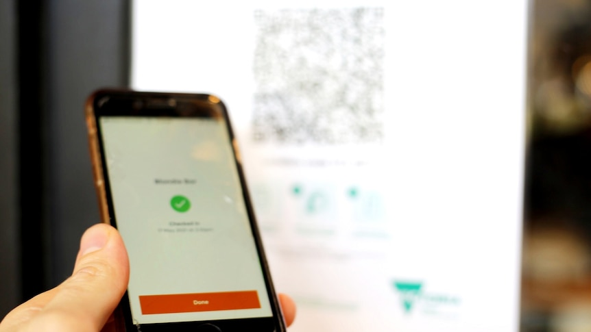 A hand holds a mobile phone with the orange Service Victoria app open to sign in with a QR code.