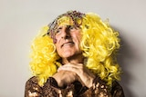 Close up of Kim Gotlieb wearing yellow-blond wig with beads, and a sequinned dress.