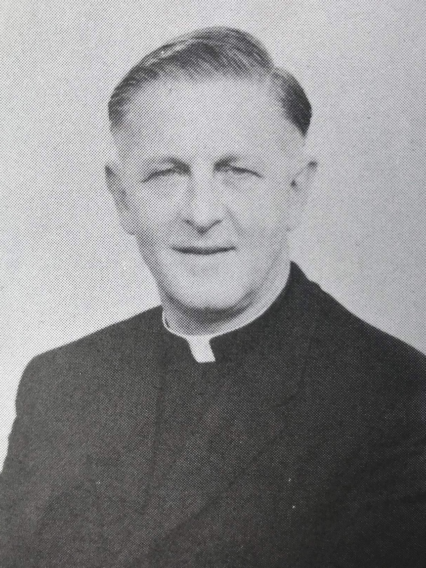 A black and white yearbook-style picture of a priest