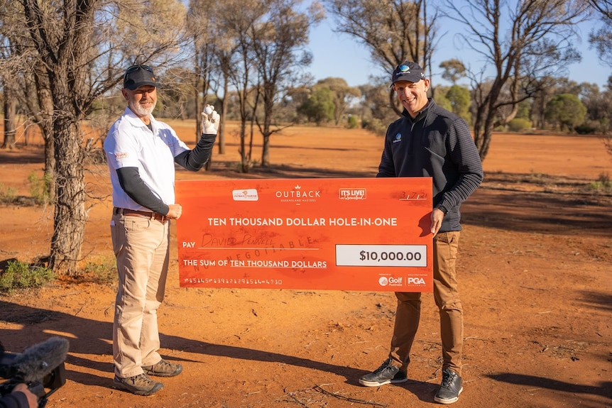 Two men hold up an orange novelty cheque on an outback red sand golf course. One holds up a golf ball.