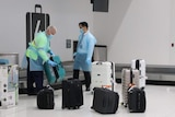 Baggage handlers at Perth Airport remove suitcases from the carousel, while wearing protective gear, including gloves and masks.