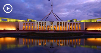 A wide-angle shot of Australia's Parliament House with a cloudy, night sky above it.