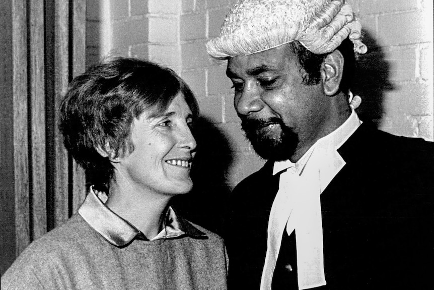A woman with short hair smiling at a man standing next to her in a judge's wig and cloak.