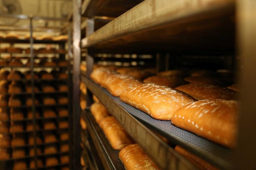Fresh bread sitting on racks at a wholesale bakery