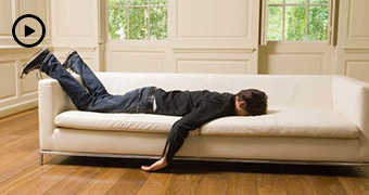 Man lays face down on a white couch with arm hanging down and feet in the air.