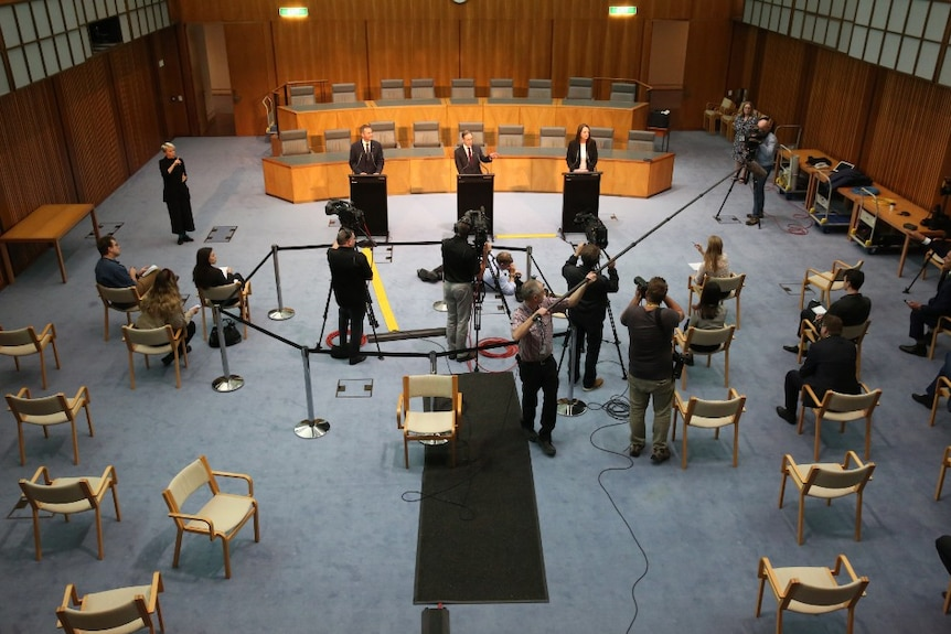 Aerial shot of three people behind podiums and camera crews, photographers and journalists spread out standing or on chairs.