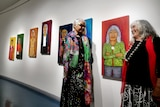 Two women smiling at each other in an art gallery