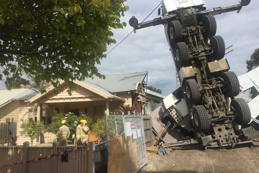 An upturned crane sits atop a damaged house, as firefighters stand in the front yard of a home next door.