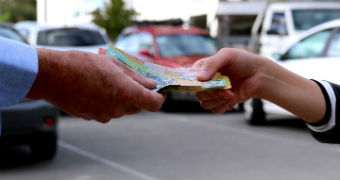 The hand of a young woman takes a wad of cash — Australian $50 and $100 notes — from the hand of an older man.