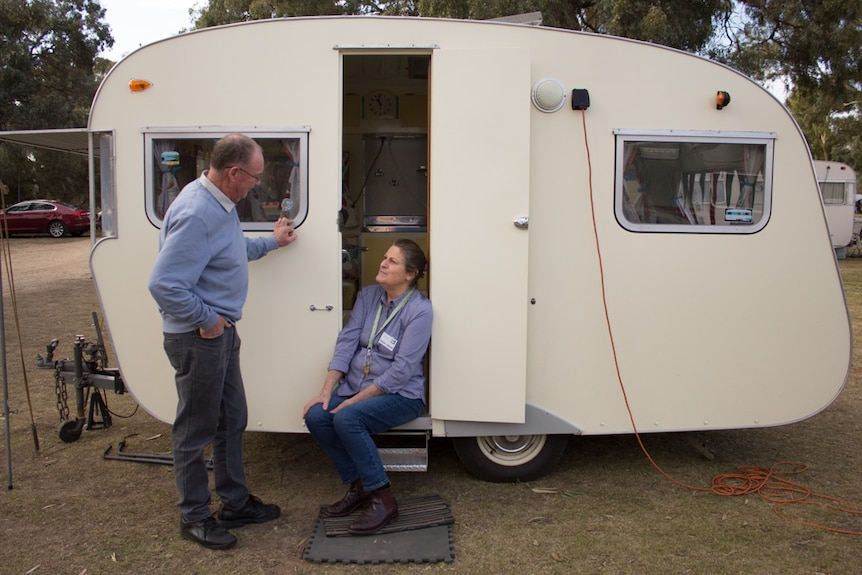 A woman sits on the steps to a small vintage caravan and looks up at her husband, who is leaning on the side of the van.