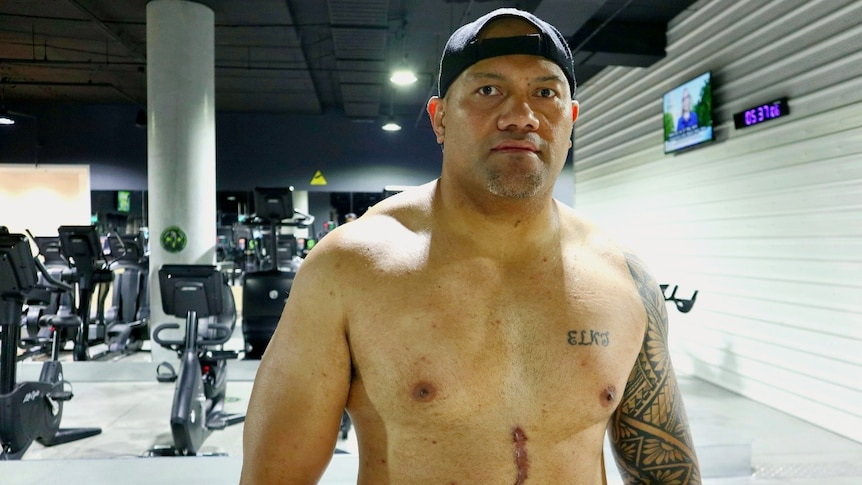 A shirtless muscly Tongan man with a scar on his stomach and wearing his cap backwards standing in a gym.
