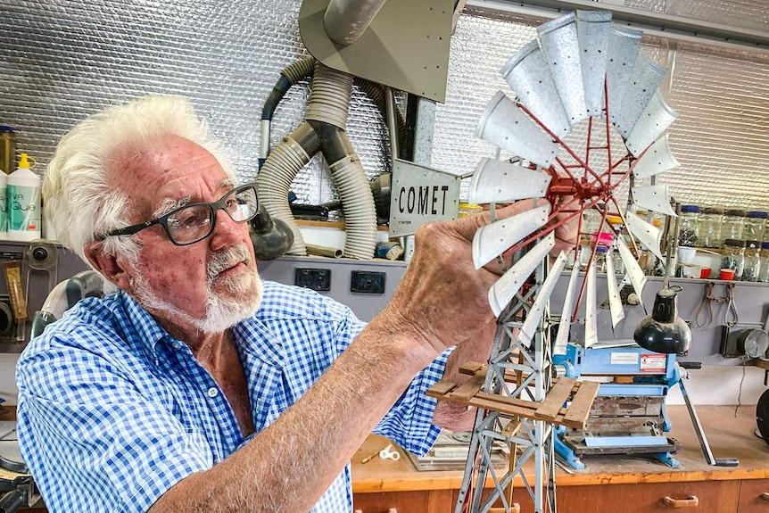 A man puts the finishing touches on a model windmill