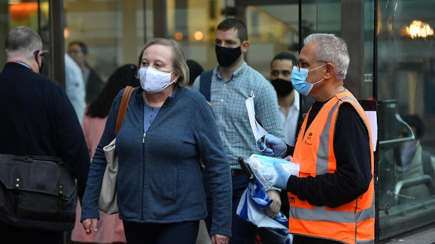 A group of commuters wear masks while walking outside.