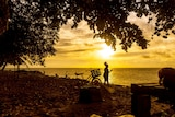 A child watches the sunset on Murray Island in the Torres Strait.