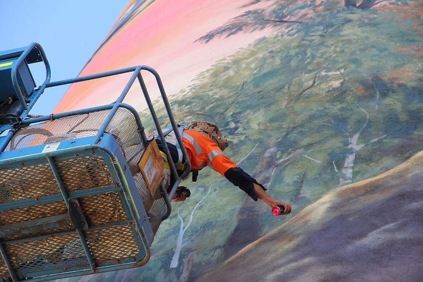 A man reaches out to spray paint a mural