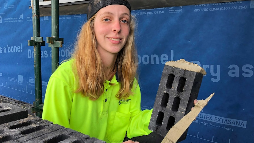 Chelsea Whelan, a bricklaying apprentice, poses with a brick and some