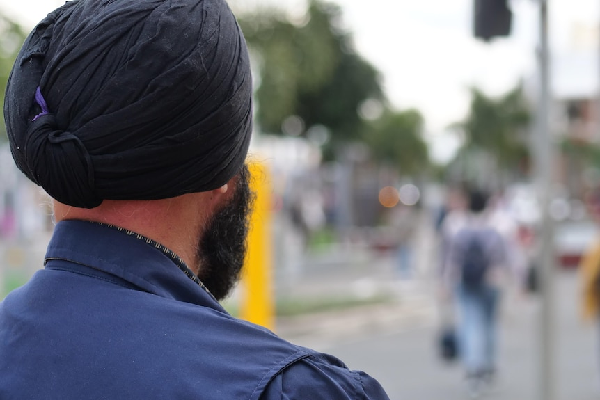 A man wearing a black turban and blue shirt looking out over a city street crossing