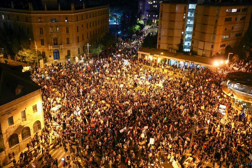 An aerial shot shows thousand of people gathered closely in a town square under lights at night.