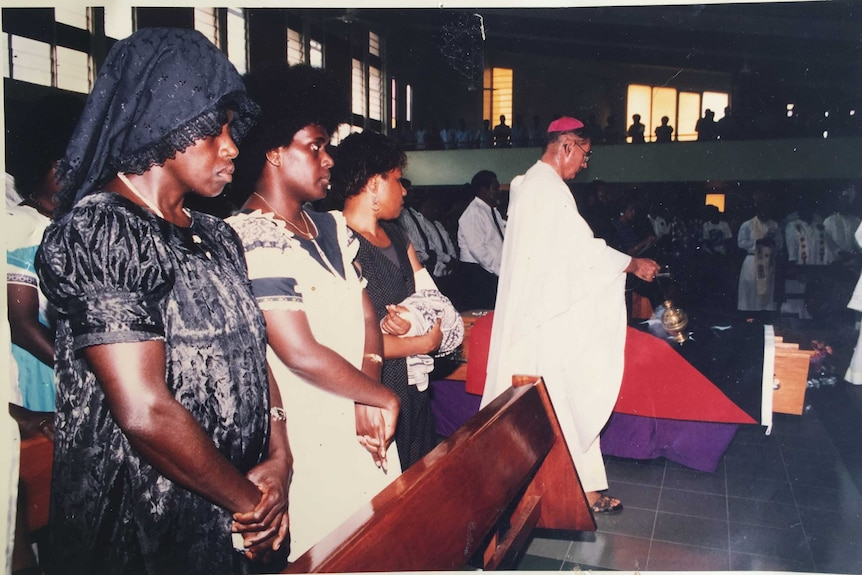 An old photo of women watching a priest next to a coffin