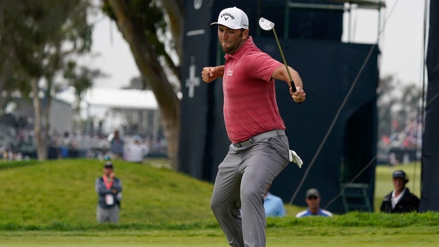 Jon Rahm punches the air while holding his putter at the US Open golf.