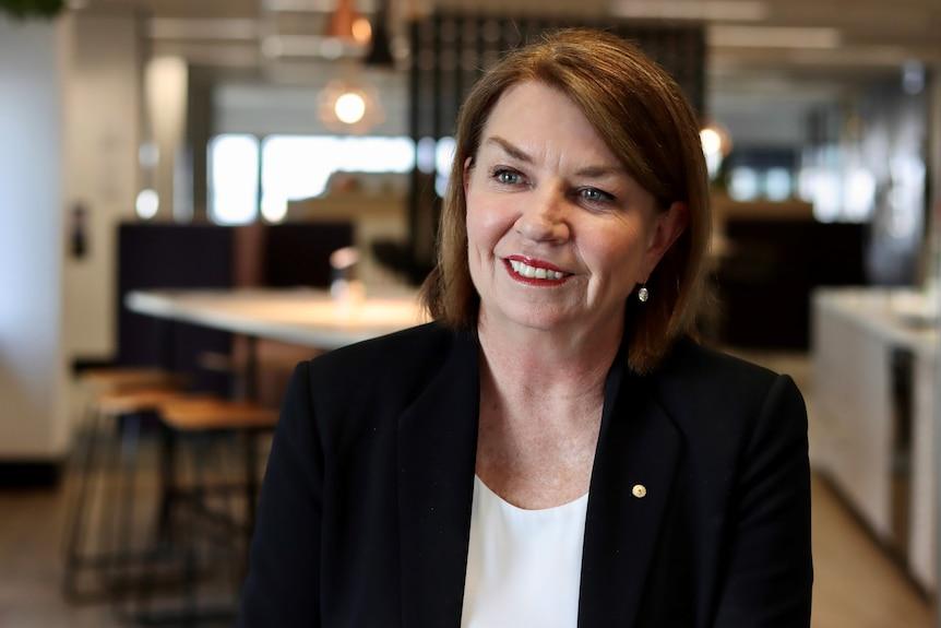 Una donna con una camicia bianca e una giacca nera si siede e sorride alla telecamera.